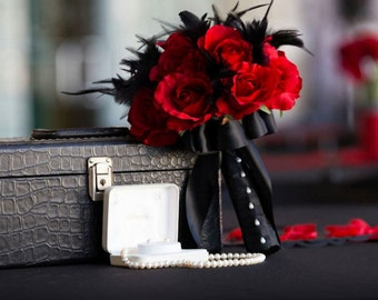 Black feather and rich red rose bouquet and boutonniere set