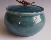 Ceramic, wheel thrown, lidded jar with tropical flower handle-shiny teal blue glaze
