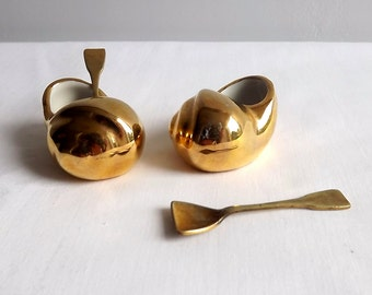 Two gold plated ceramic snails with spoons by Limoges, mustard pots or salts