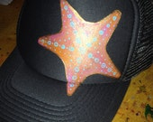 Slate grey trucker with hand painted goldy/sunset starfish. Turquoise detail.