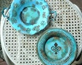 Vintage metal plates, painted, aged and distressed,turquoise blue, one with a fleur de lis detail, one with handles, rusted decor
