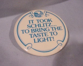 "Pin Back Celluloid Badge, ""It Took Schlitz To Bring The Taste To Light !"