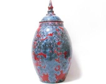 Red ceramic lidded jar with deep blue crystals