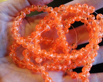 130 approx. 6 mm drawbench transparent glass beads, neon orange, with spray painted white lines, hole 1.3-1.6 mm