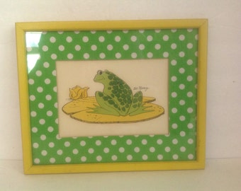 vintage 70's Bob Mesrop black ink and hand colored whimsical frog on lily pad with green and white polka dot mat and yellow frame