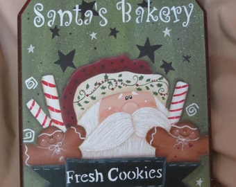 Santa's Bakery is selling Fresh Cookies.  Santa with gingerbread and candy canes.