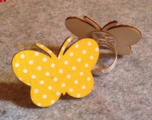 Striking butterfly ring wooden butterfly covered in Yellow polka dot fabric and set onto a silver toned metal adjustable ring