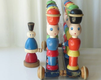 Delightful vintage children's wooden pull toy with brightly colored peg men. Eleven men in all.