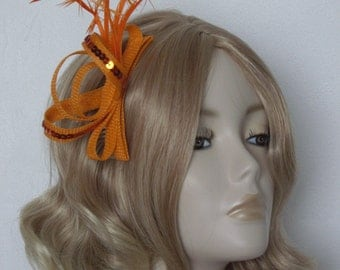 NEON ORANGE FASCINATOR, Made with sinamay, Knotted biot feathers,sequins,on a 4in comb