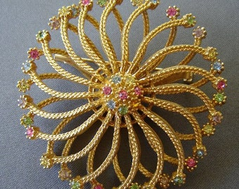 Vintage 60's Twirling Caged Sunburst Brooch In Layered Goldtone Metal Edged With Bright Sparkling Star Shaped Rhinestones