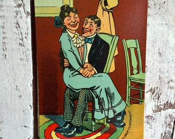 Antique post card lovers girl sitting on boys lap, lovers sitting together