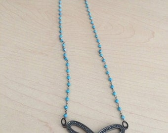 Blue wire wrapped necklace with black stone bow