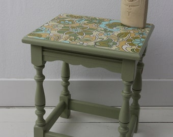 Green side table with vintage wallpaper with blue and green flowers