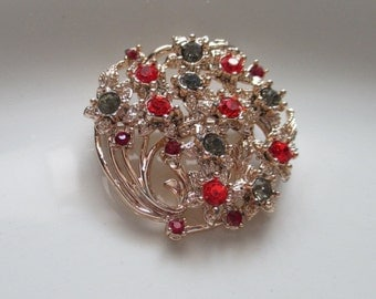 Brooch/Vintage gold toned brooch with red, blueish green and orange gems