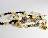 Glittering Gold Black & Pearl Flower Charms Set of Three 8 inch Stretch Glass Bead Bracelets