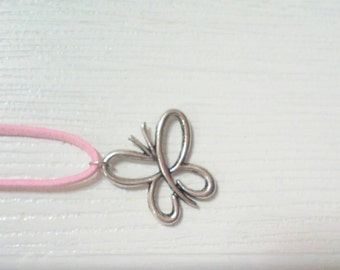 Silver butterfly hanging on pink soft leather.