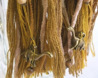 Large fabric tassel earrings in earthy tones with dinosaurs in antique bronze color as ear clip