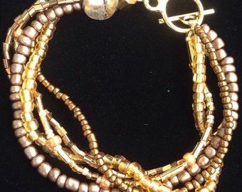 Gold, copper and bronze multi strand beaded bracelet