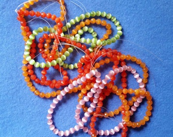 Six Strands of 5mm Faceted Round Cats Eye Glass Beads - pink, light green, orange, dark orange - bead destash