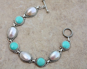 "Beautiful bracelet with Turquoise and pearl. Marked 925 Sterling Silver. 7.5"" long, 1/2"" wide weighs 21gm"