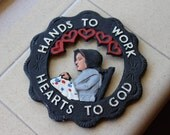 VINTAGE black iron hand painted trivet, Amish woman. Pennsylvania Dutch.  Hands to Work,Hearts to God