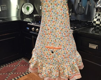 Apron done in mod, retro cotton with coordinating orange and white checks and dots.