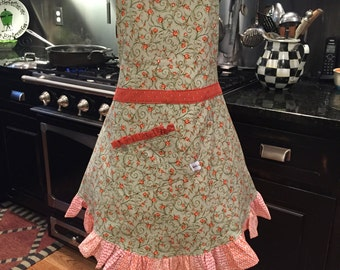 Apron done in sage green cotton print with orange accent cottons