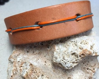 Unisex Natural Leather Cuff with Orange Leather and Turquoise Linen cord accent and a metal closure.