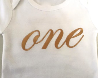 Word ONE or any Number written out,in any color thread with Name one back, Embroidered on Onesie or Shirt
