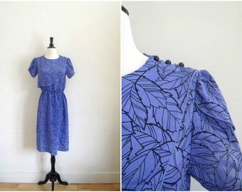 Vintage purple and black leaf print dress / retro violet novelty dress with a bib detail front