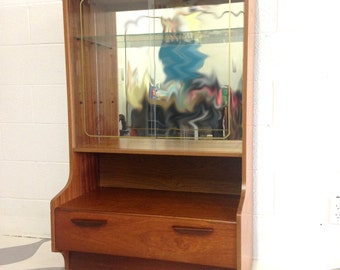 mid century modern cabinet in teak with one drawer and glass door