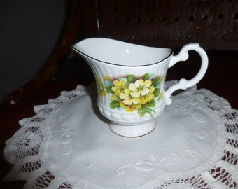 Royal Minster fine bone china made in England small milk jug or creamer showing yellow dog roses on green foliage.