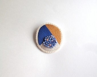 Hand embroidered jewelry geometric brooch tan, blue and cream with blue and white African beads on cream muslin with cream felt backing
