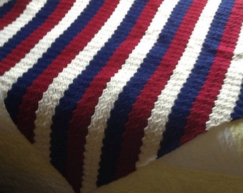 Crocheted lap afghan in creams, dark reds and navy blues.
