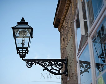 Street photography, lamp and reflection of lamp in the window, old street lamp, lantern and blue sky in background