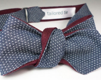 Indigo cotton chambray men's bow tie woven in an intricate foulard pindot pattern... over fine burgundy linen blades. Slim rev adj self-tie