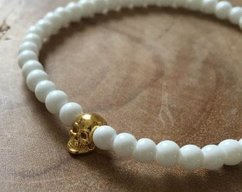 White Gold Skull: an elastic beaded bracelet with goldtone skull and white glass beads.