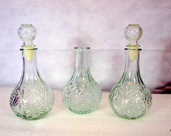 Three decanters, clear pressed glass, star burst design, 2 with stoppers, vintage