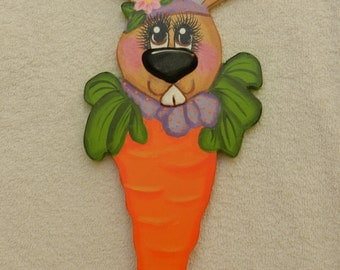 Easter bunny looking over carrot wall hanging