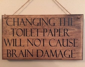 Changing the toilet paper will not cause brain damage sign