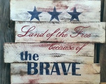Land of the free, because of the brave sign. Reclaimed cedar fence panel, hand painted and distressed. Hand painted lettering