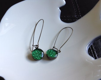 So much drama in such a small space. Kidney shaped, green glitter drop earrings.