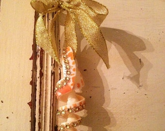 A gold bedazzled shelll ornament with a gold bow. Christmas, gold, shell, seashell, beach themed, beach, ribbon, beach cottage, beach house