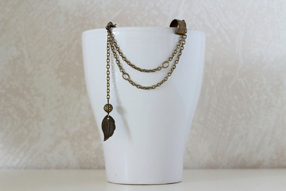 A white mug with a bronze ear cuff of chains and dangling leaf on top