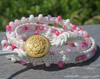3mm pink shades of Czech glass beads, white leather, white cord wrapping, wrap bracelet and a gold toned crest button - fit for royalty!