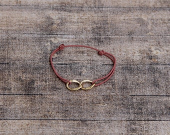 Infinity bracelet : golden infinity sign on a bright powder pink synthetic lacings. Adjustable baby pink gold bracelet