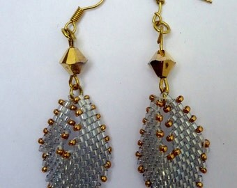 Dangling beaded earrings in silver delicas and gold seed beads.