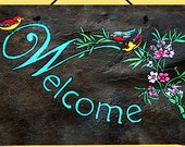 Hand painted slate welcome sign has cute little birds hanging out on branches with flowers.