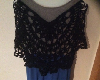 This is a black, crochet shawl with a blue flower