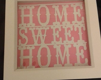 Home sweet home papercut picture mounted on a coloured background